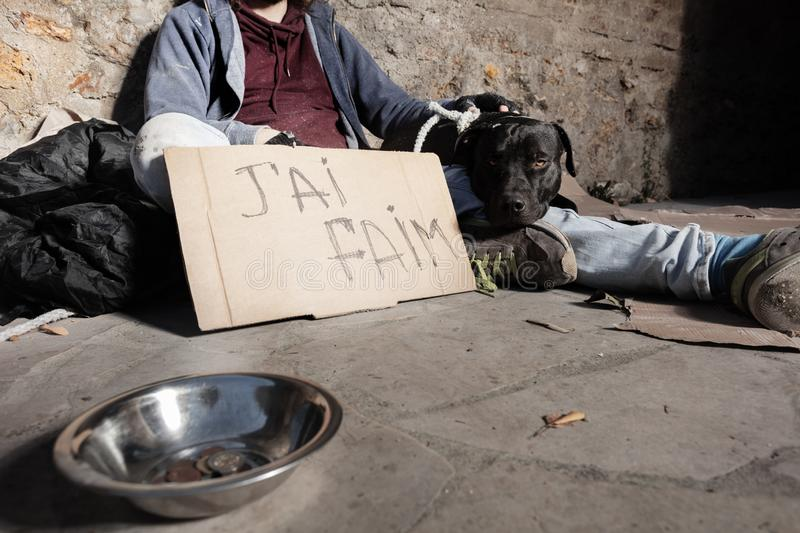 Beggar and dog sitting next to alms bowl on street stock photography