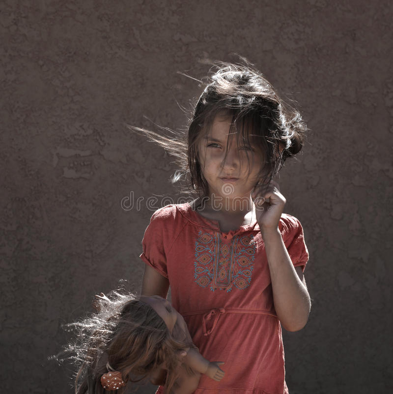 Beggar Girl with doll royalty free stock photography