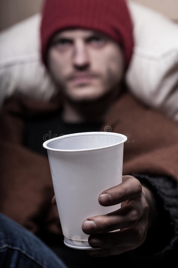 Beggar holding a cup for coins stock images