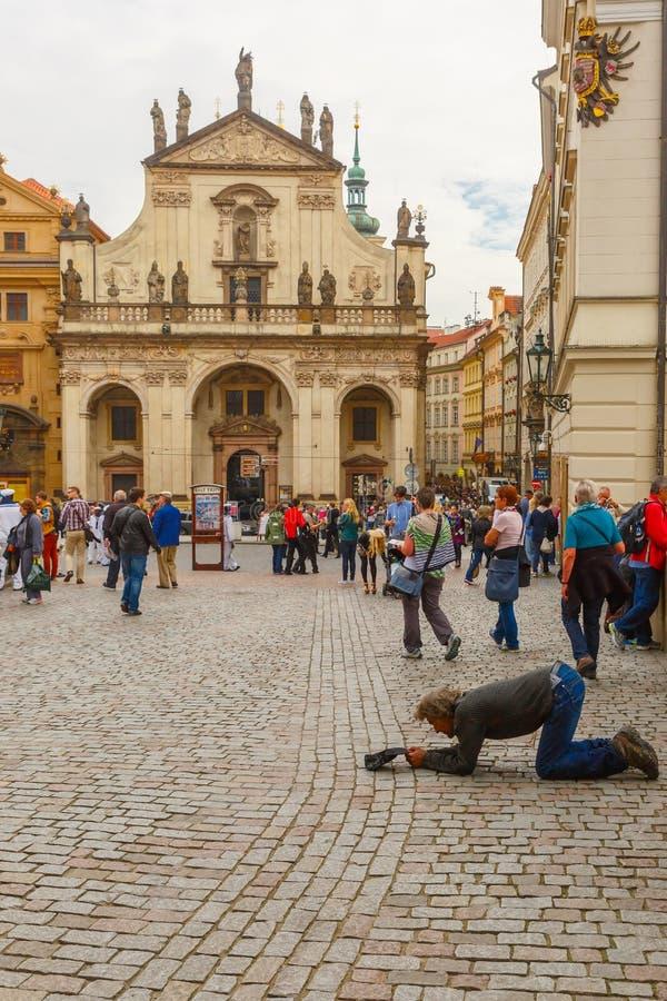 Beggar, homeless kneeling begging in Prague. Prague, Czech Republic - October 6, 2014: Beggar, homeless kneeling begging near Charles Bridge in Old Town stock images