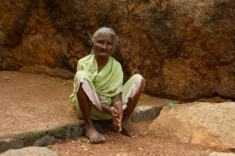 Beggar in the park. An elderly woman begs in the park of stones. India, Tamil Nadu, Mahabalipuram, 2016
