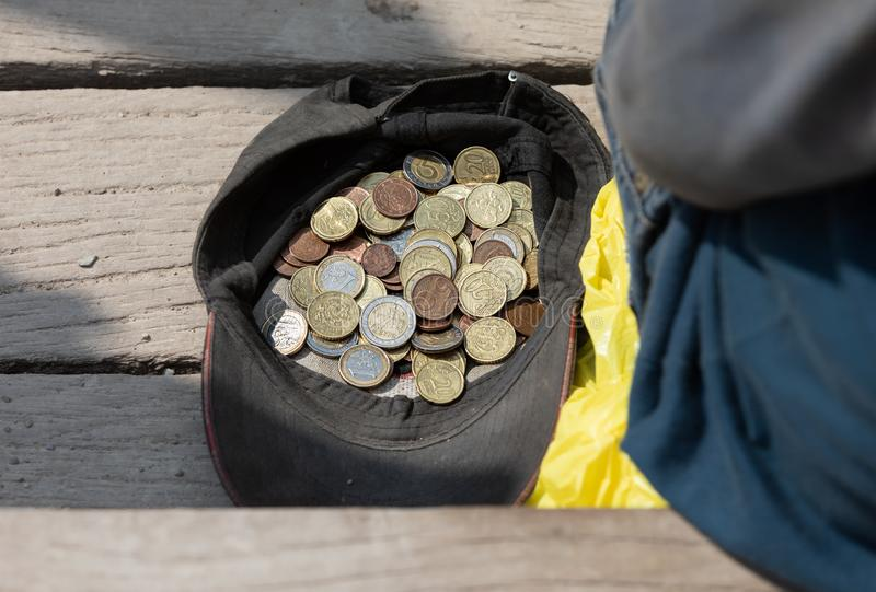 A beggar sits near a cap with coins stock photography