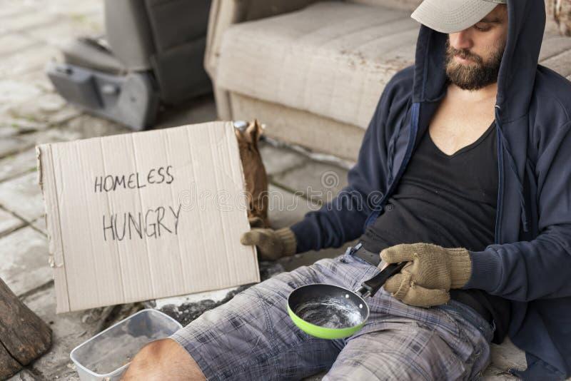 Homeless beggar in the street. Beggar wearing hoodie over cap and fingerless gloves, sitting in the street, begging for money stock images