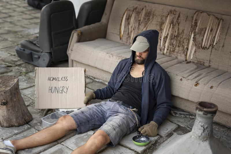 Homeless beggar in the street. Beggar wearing hoodie over cap and fingerless gloves, sitting in the street, begging for money royalty free stock photography