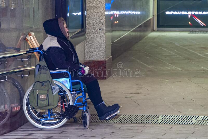 Beggar in a wheelchair asks for alms. Moscow,Russia-February 15,2020.A beggar in a wheelchair asks for alms. In Russia, many people with disabilities live below royalty free stock photo