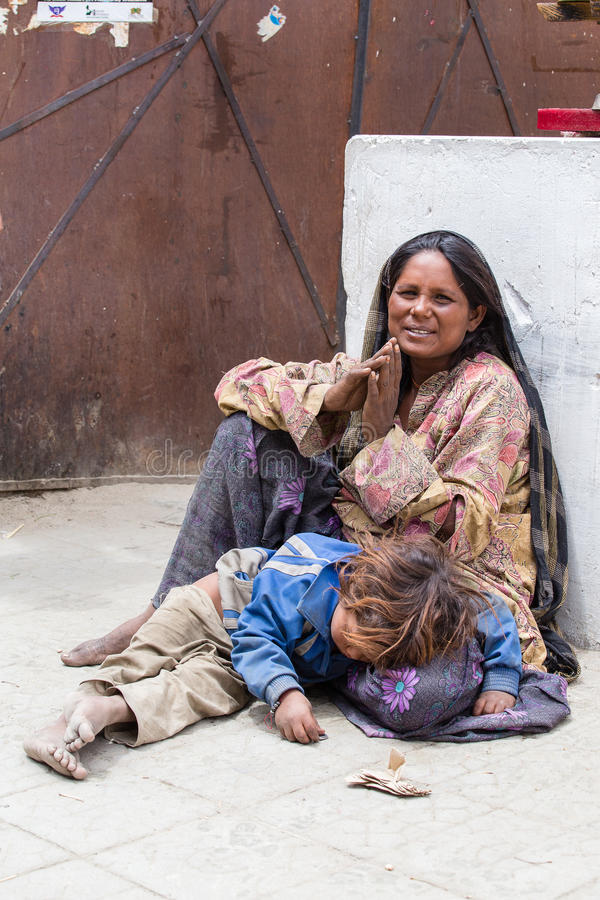 Beggar woman with a child begging in Buddhist temple in Leh, Ladakh. India. LEH, INDIA - JUNE 24, 2015: Unknown beggar woman with a child begging near Buddhist royalty free stock photos