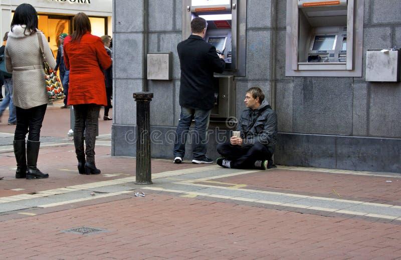 Begger bij een ATM-Machine stock fotografie