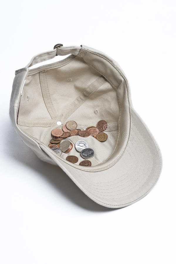 Begging for change. Baseball cap with some canadian change in it royalty free stock image