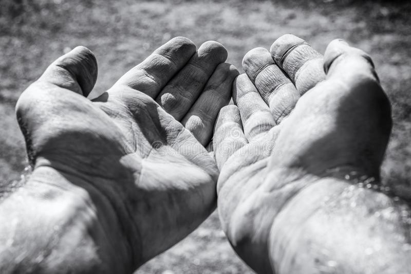 Begging dirty hands as a sign of poverty stock photo
