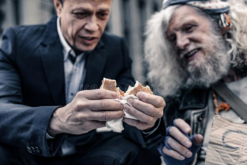 Sincere kind man in office costume sharing sandwich with homeless man royalty free stock photo