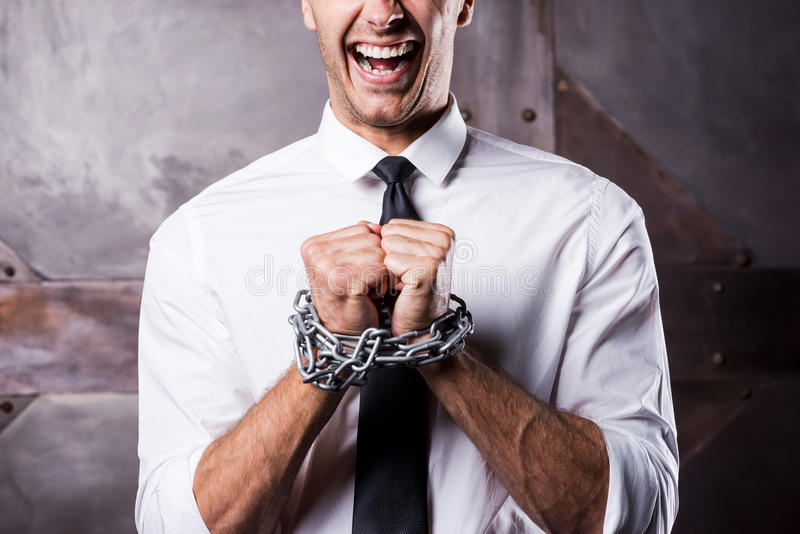 Begging for freedom. Close-up of furious young businessman grimacing while being trapped in chains royalty free stock photography