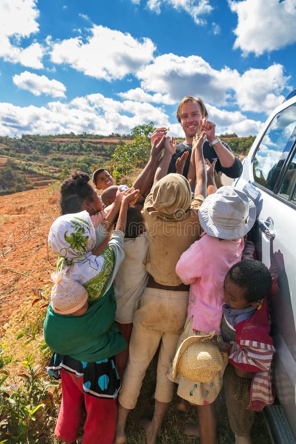 Begging kids. Kids begging for candy from a tourist on the side of the road near Ambositra, Madagascar, on September 7, 2013 royalty free stock photo