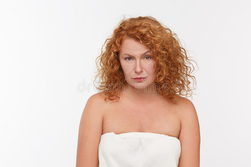 Begging mature woman. Picture of begging mature or senior woman with red hair looking at camera while posing on whte background in studio. Emotions concept stock images