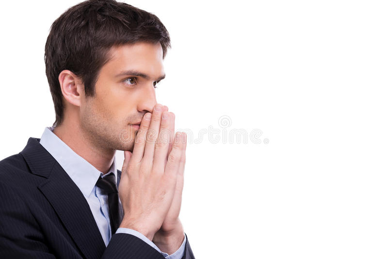 Begging for success. Side view of thoughtful young man in formalwear holding hands clasped near face and looking away while standing isolated on white royalty free stock photography