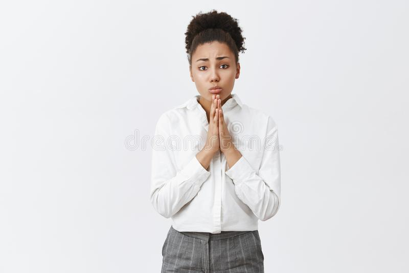 Begging you for mercy. Portrait of upset cute african-american in white shirt and pants, holding hands in pray near royalty free stock images