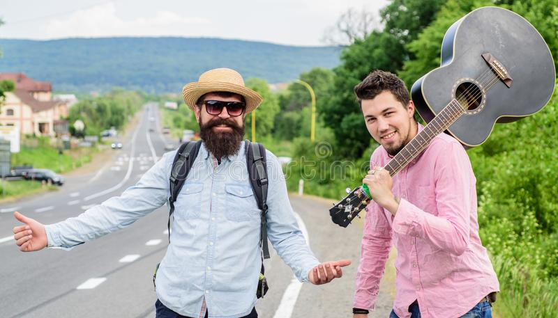 Begin adventure. Travelers with backpack and guitar ready to strat new journey. Men at edge of road hitchhiking. Friends. Gathered travel together. Men royalty free stock photo