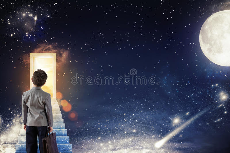 Begin a course for future life. Boy climbs the stairs to a door with sunlight on a starry sky with the moon and the stars stock image