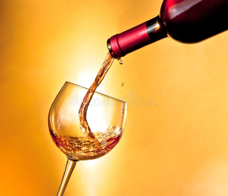 Begin filling red wine in the glass tilted. On golden background stock photography