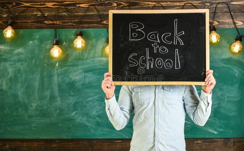 Begin van schooljaarconcept De leraar houdt bord voor gezicht De mens heet studenten, bord op achtergrond welkom royalty-vrije stock afbeeldingen