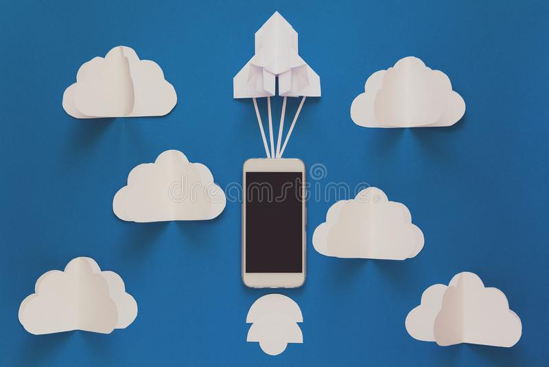 Beginnen Sie oben oder schnelles Verbindungskonzept Die Produkteinführungspapierrakete mit intelligentem Telefon auf blauem Himme stockfotografie