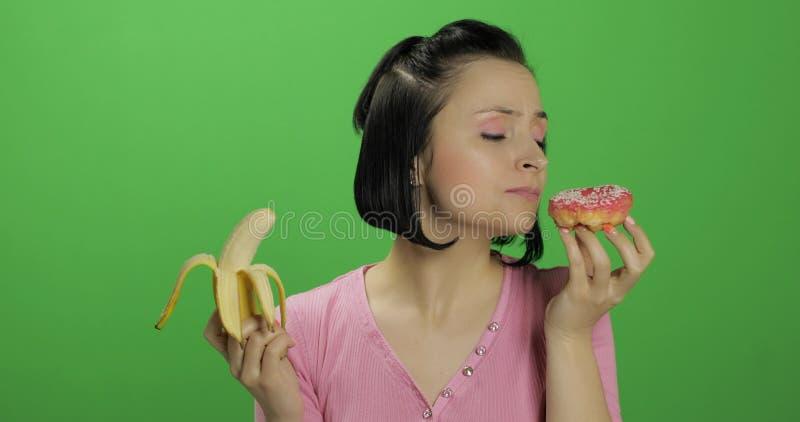 Beginnen von gesunder Ern?hrung Lehnen Sie ungesunde Fertigkost ab Auserlesener Donut oder Banane zu essen stockfoto