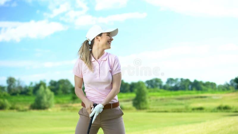 Beginnende vrouwelijke golfspeler die club vasthoudt en glimlacht, blij schot, overwinning stock foto's