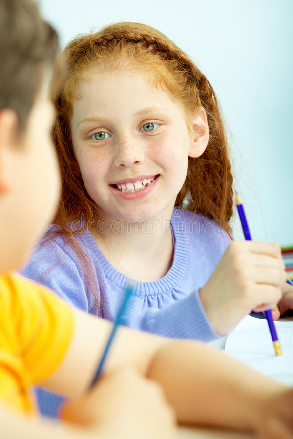 Beginner. Portrait of smart schoolgirl looking at classmate at drawing lesson royalty free stock photography