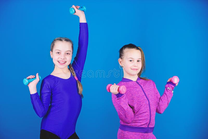 Beginner dumbbells exercises. Children hold dumbbells blue background. Sport for teens. Easy exercises with dumbbell. Sporty upbringing. On way to stronger royalty free stock image