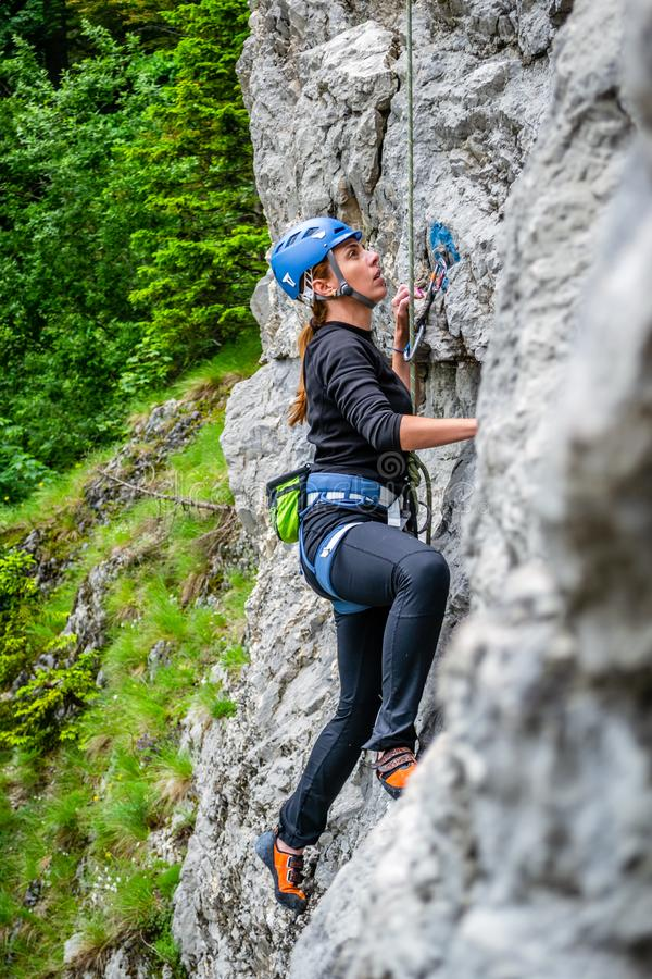 Beginner female climber on top rope, climbing a sport route near Sinaia town, in Bucegi mountains, Romania, on a chilly Spring day stock images