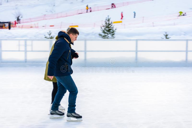 A beginner man rides a skating rink in an open-air ski resort. A beginner men rides a skating rink in an open-air ski resort 2019 royalty free stock photos