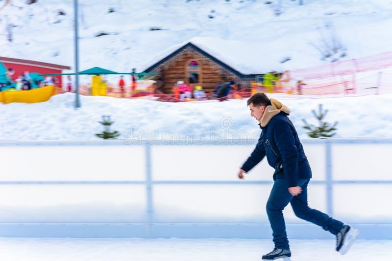 A beginner man rides a skating rink in an open-air ski resort. 2019 royalty free stock image