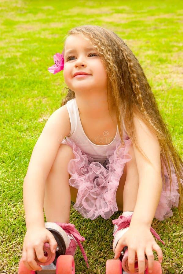 Beginner preschool маленькой девочки сидя в траве с ее коньками ролика, в предпосылке травы стоковые фото