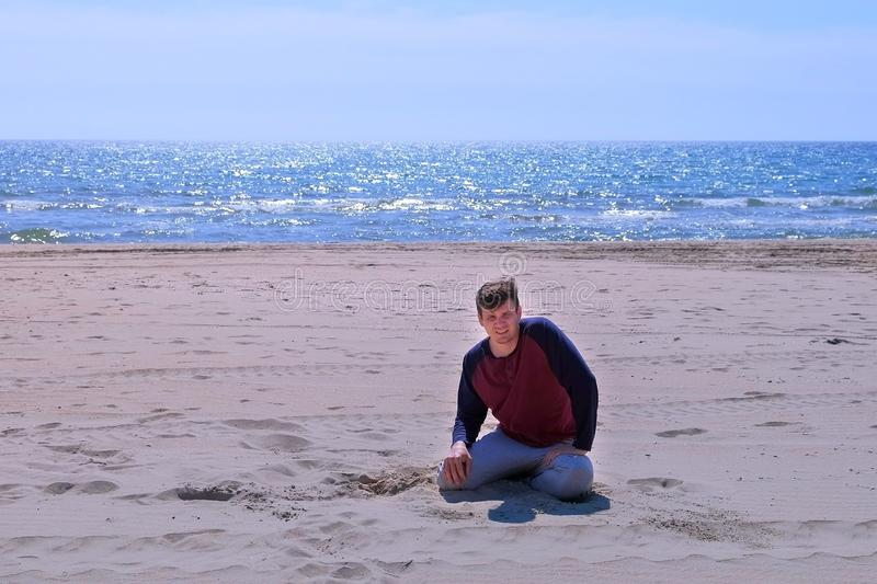 Beginner tired man fall on the sand beach after jogging at seaside. stock image