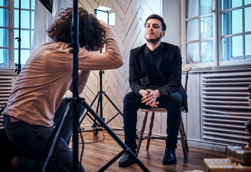 Beginnerfotograaf bij een fotospruit in een studio met een elegant geklede kerel stock fotografie