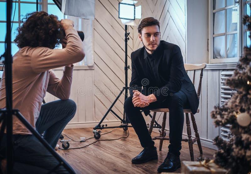 Beginnerfotograaf bij een fotospruit in een studio met een elegant geklede kerel royalty-vrije stock foto's