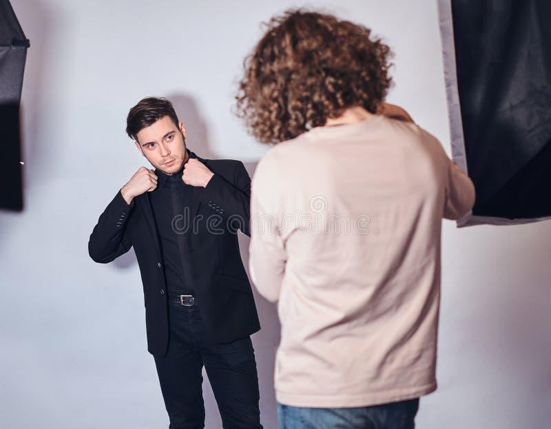 Beginnerfotograaf bij een fotospruit in een studio met een elegant geklede kerel royalty-vrije stock foto