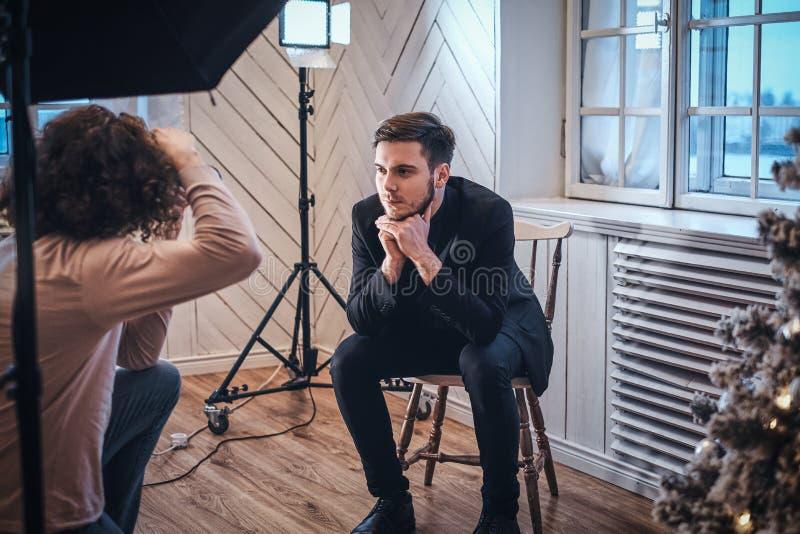 Beginnerfotograaf bij een fotospruit in een studio met een elegant geklede kerel stock afbeelding