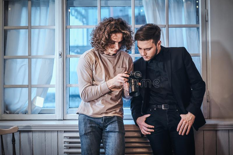 Beginnerfotograaf die de resulterende foto's met zijn klant in de studio doorbladeren royalty-vrije stock afbeelding