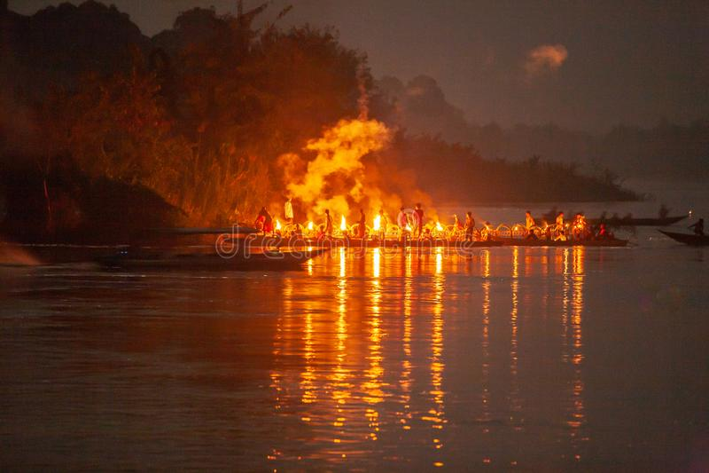 Beginnermonniken en jongen die een kaars op houten boot in het festival van de verlichte bootoptocht aansteken Mekong Rivier, Don royalty-vrije stock foto