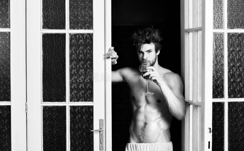 Beginning great evening. Man with sexy torso drink wine. Bachelor sexy body. Sexy attractive macho tousled hair coming. Out through bedroom door. Sexy lover stock images