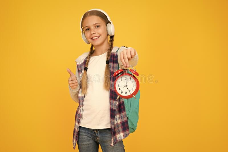 Beginning of lessons. Time go school. School time. Happy girl hold alarm clock counting minutes. Knowledge day. Classes. Schedule. Schoolgirl hold alarm clock royalty free stock images