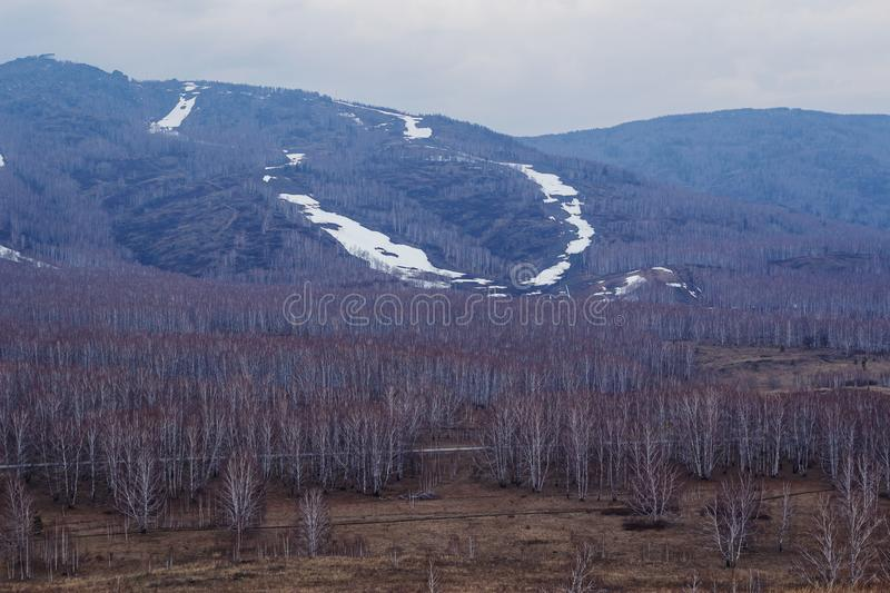 The beginning of spring in the mountains, the sad gray misty landscape, ski slopes royalty free stock image