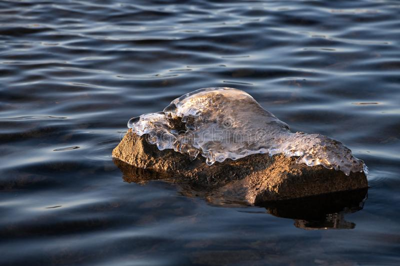 Beginning of winter. Relaxing view of a stones in the water with an ice cap at sunset stock image