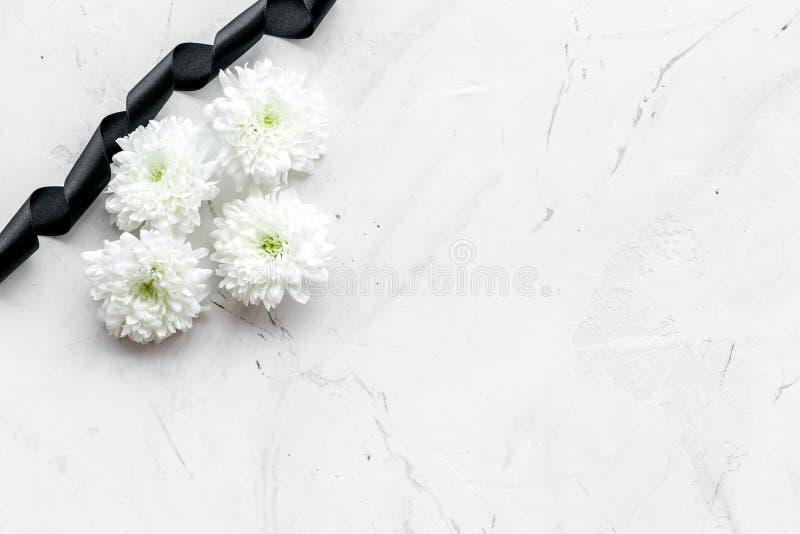 Begräbnis- Symbole Weiße Blume nahe Trauerflor auf weißem Draufsicht-Kopienraum des Steinhintergrundes stockfoto