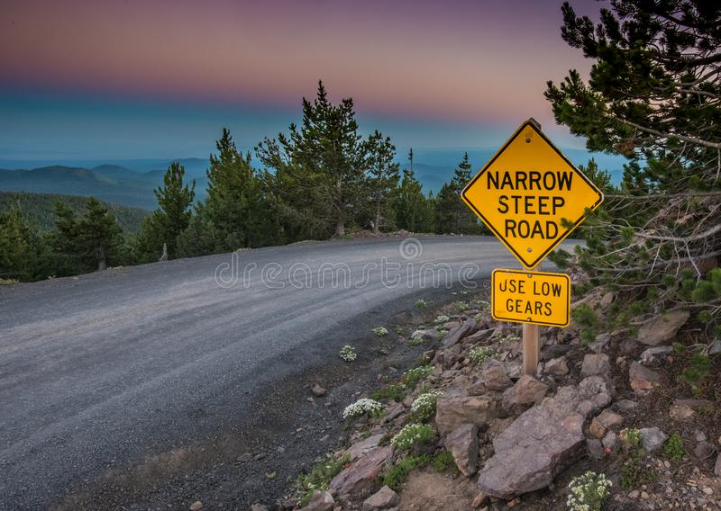 Begränsa det branta vägmärket på solnedgången fotografering för bildbyråer