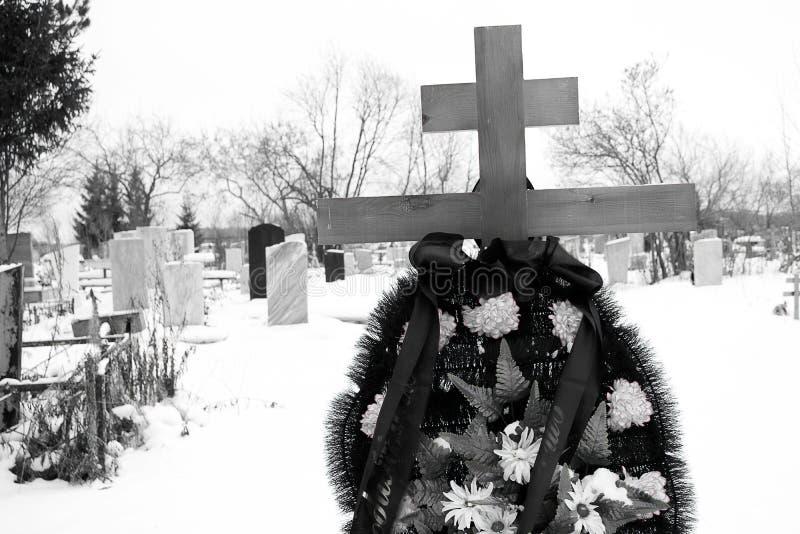 Begraafplaats tijdens de winter in de voorgrond een kruis op het graf met een kroon van kunstbloemen, in de achtergrondgrafsteen royalty-vrije stock fotografie