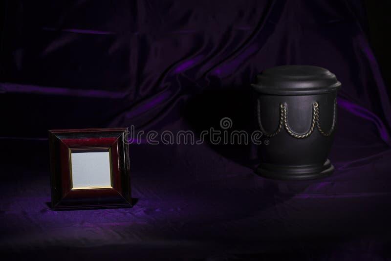 Begraafplaatsurn met gouden decoratie en leeg klein zwart het rouwen kader royalty-vrije stock afbeelding