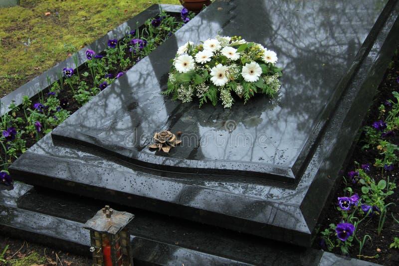 Begrafenisbloemen op een graf stock foto's