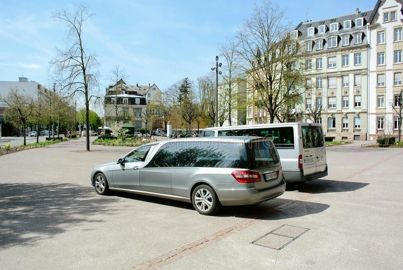 Begrafenisdielijkwagen en bestelwagen voor de Kerk wordt geparkeerd royalty-vrije stock fotografie