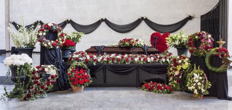 Begravning kista som dekoreras med kransar, i avskedkorridoren, panorama royaltyfri fotografi